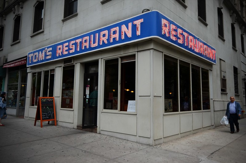 "A photo of the famous diner from Seinfeld. It's on the corner of a concrete building with a large sign that says ""Tom's Restaurant"" on the side"