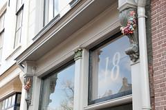 <p>Huize 'De Moriaan', aanzicht van de gevel op straatniveau. Let op de sculptuur van bloemtrossen aan weerzijde. Foto: Anna van Kooij.</p>