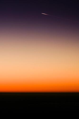 sunset orange plane contrail purple