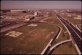 Junior High School Football Team Plays On Field Surrounded By Freeways. Municipal Stadium In Left Background, August 1973
