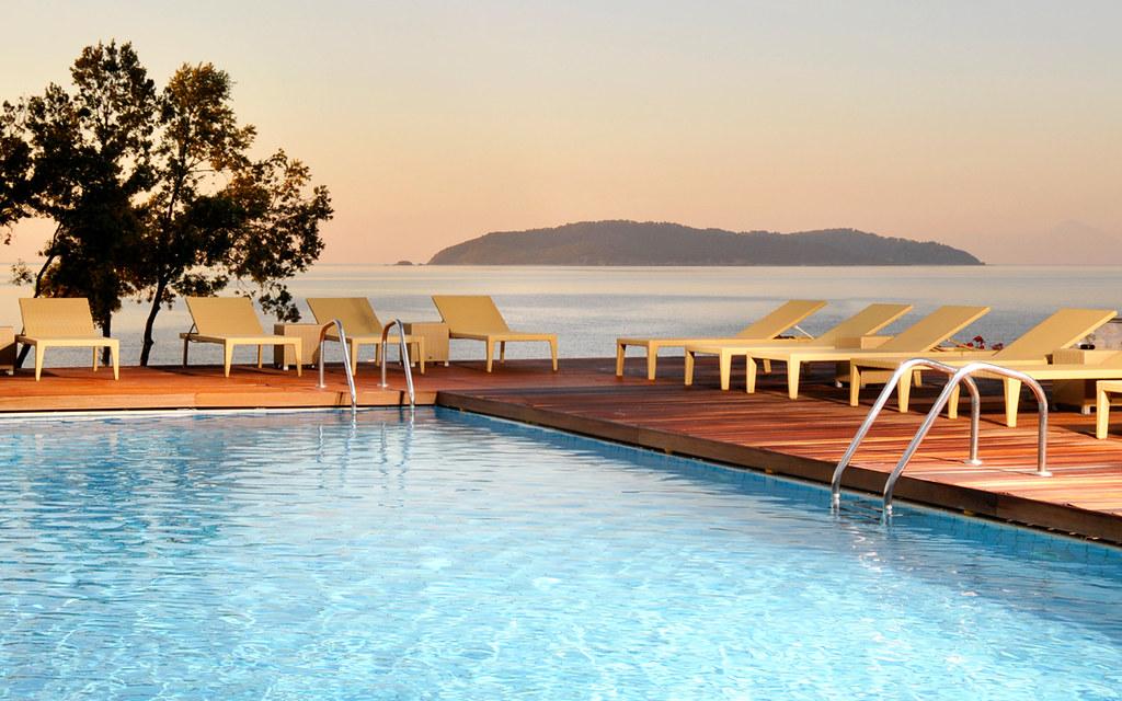 Yellow sun-bed chairs around the swimming pool of the Luxury Hotel Kassandra Bay