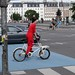 Fashionable red jumpsuit woman riding a short john cargo bike by Steven Vance
