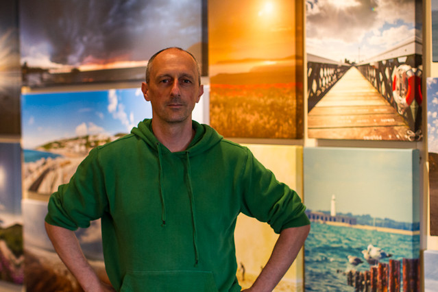 Me, posing in front of my Canvases at the Ocean Seen exhibition.