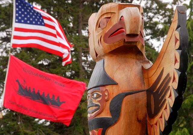 Eagle Totem with American and Suquamish Tribe flags, Suquamish, Washington, USA