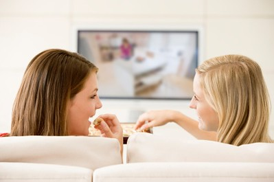 Two women in living room watching television eating chocolates s | by esm|Fitness - Sean Hammers