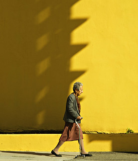 Woman with Cane Walking Past Yellow Bldg (b)