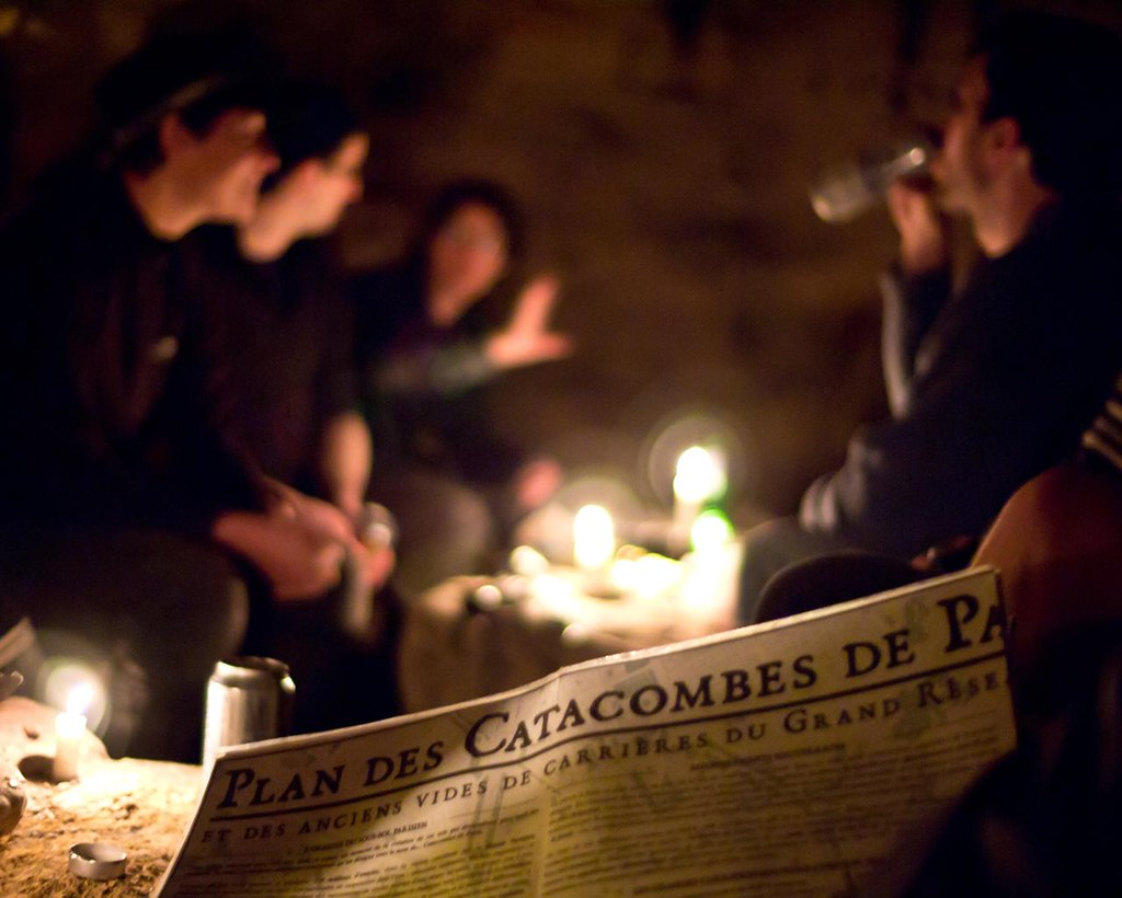 photo of people sitting in a catacomb in Paris