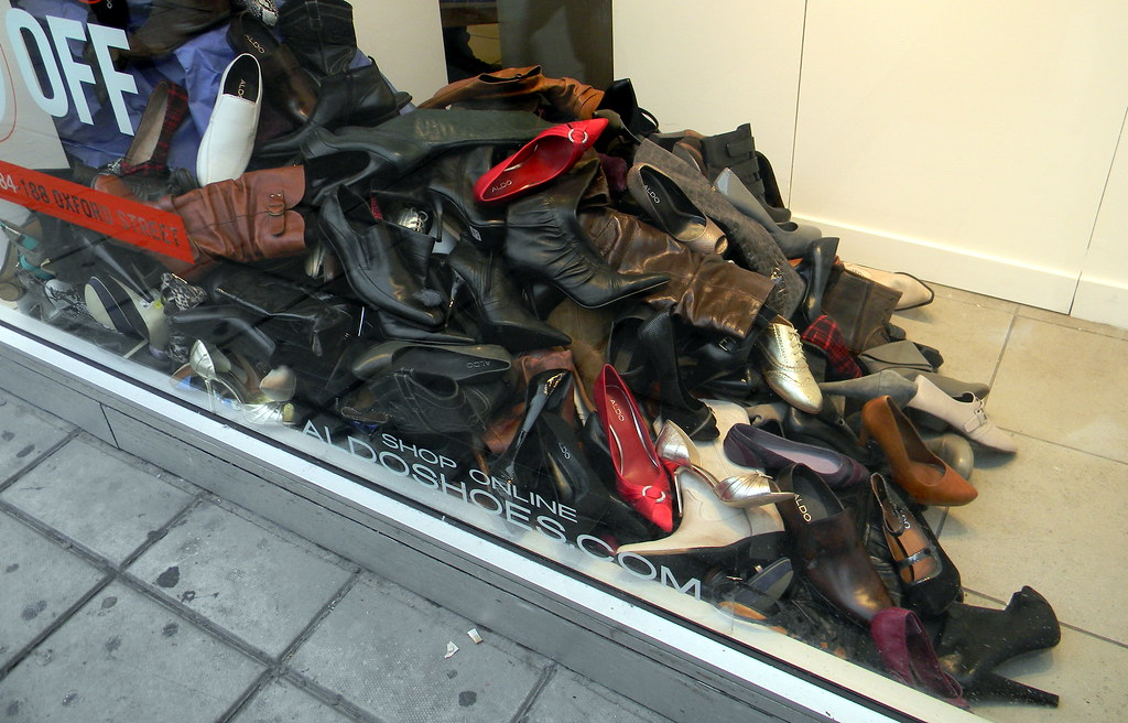 ladies shoes boots piled up in shop window Oxford street L