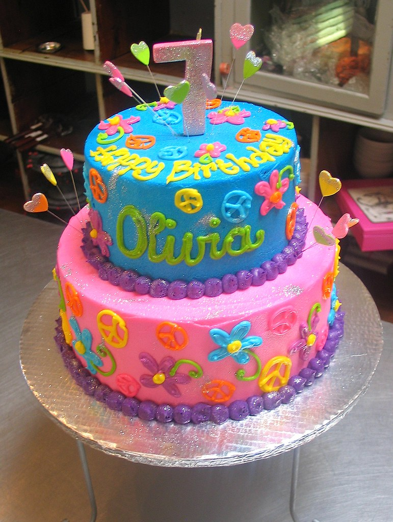 2-tier Wicked Chocolate cake iced in pink & blue butter icing decorated with a 3D glittered #7 & piped hippie themed decor