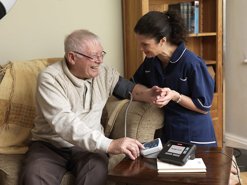 Telehealth - Older man and nurse using blood pressure | by Tunstall Telehealthcare