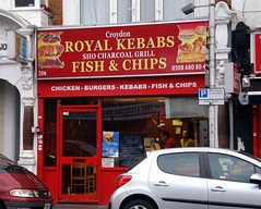 """A ground-floor bright red shopfront with a large window and sign above reading """"Croydon / Royal Kebabs / Sho [sic] Charcoal Grill / Fish & Chips""""."""