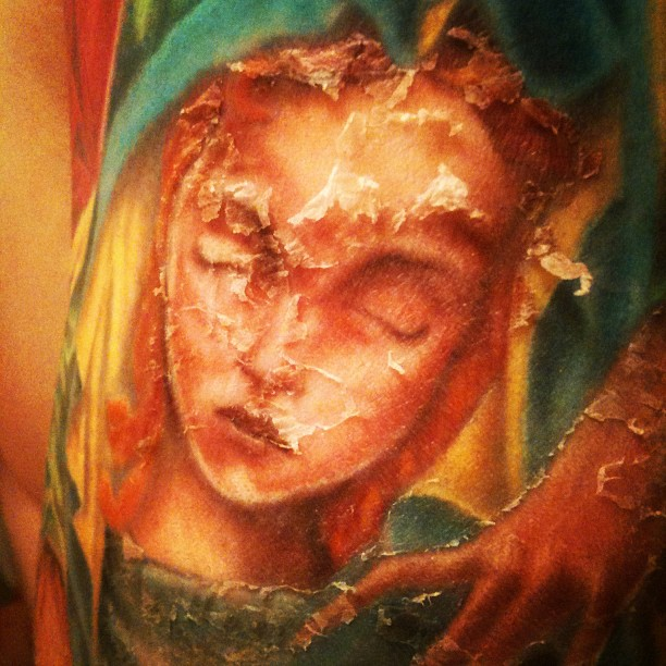 The Virgin Mary's peeling face. My tattoo as it heals.