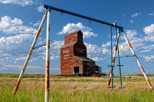 old blue sky canada building green history abandoned industry field grass playground set clouds rural vintage fun town exercise antique ghost rustic elevator farmland structure swing storage historic silo western coop recreation swinging saskatchewan agriculture desolate deserted bents agribusiness