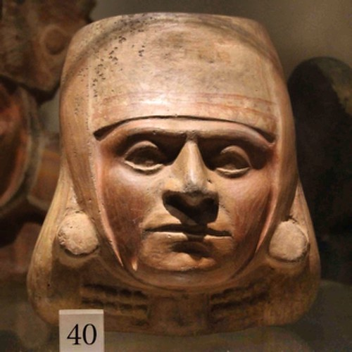 Pottery portrait head, shows a man wearing a cloth headdress and ear spools. The ancient Moche wore these headdresses as protection from dust and the sun. Moche culture, Phase IV. AD 400-600. 0.8994/35 Living Cultures. The Manchester Museum.