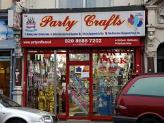 "A ground-floor terraced shopfront.  The sign above reads ""Party Crafts"" in cursive, with illustrations of a birthday cake and a bunch of balloons on either side.  The fully-glazed frontage is filled with banners, statues, stuffed toys, and other party paraphernalia."