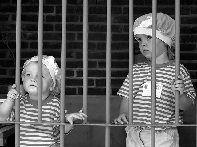 Niños tras unos barrotes