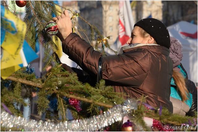 Une Kiévienne accrochant des boules de Noël sur un sapin situé devant l'hôtel de ville, Kiev, Ukraine - 24/12/2013 - photo Bernard Grua DR