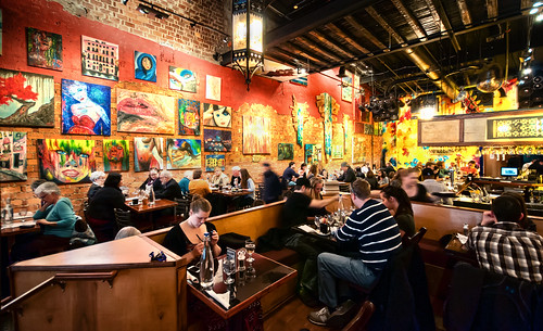 a busy restaurant filled with patrons and paintings