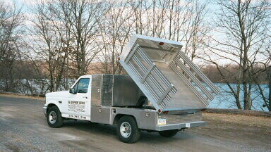 Flatbed pickup truck bed with dump hoist