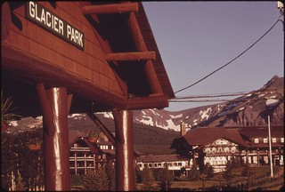 East Glacier Park, Montana, passenger train station in the foreground frames some of the grandeur which attracts travelers to the area, June 1974