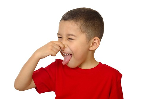 kid holding his nose from bad odor, isolated on white | by mmntz