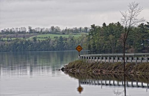 road lake reflection roadsign