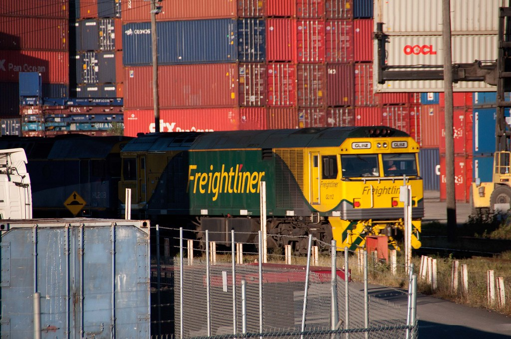 Freightliner GL112 is dwarfed by a wall of containers by John Cowper