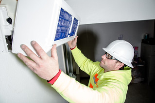 Construction worker, Jake Holmgren, installs new heating system inside resident's home in South Seattle. | by EE Image Database