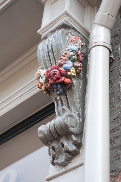 Huize de Moriaan, detailfoto van een sculptuur van een bloementros aan de gevel op straatniveau. Foto: Anna van Kooij.