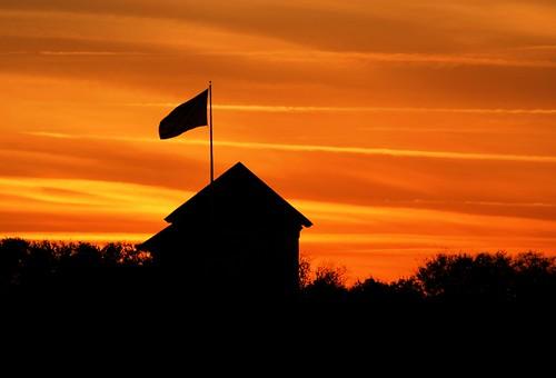 city roof sunset mist tower rooftop silhouette downtown glow unitedstates florida flag americanflag treetops roofline thewave oldglory northflorida orangeglow wavingflag saintaugustineflorida cloudlines theoriginalwave