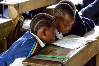 Schoolchildren read a textbook. | by Community Eye Health