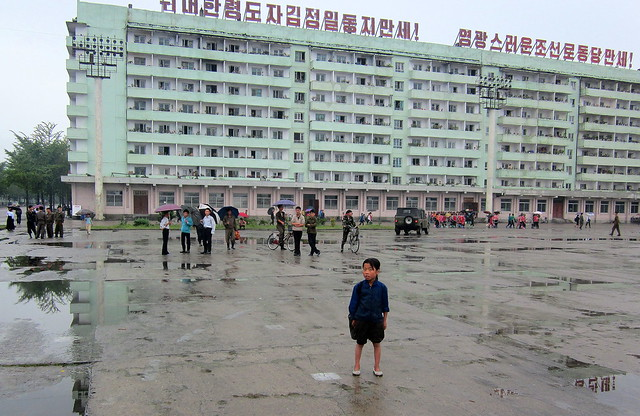 North Korea Hamhung drab apartment building and lost-looking kid who drew a paparazzi crowd