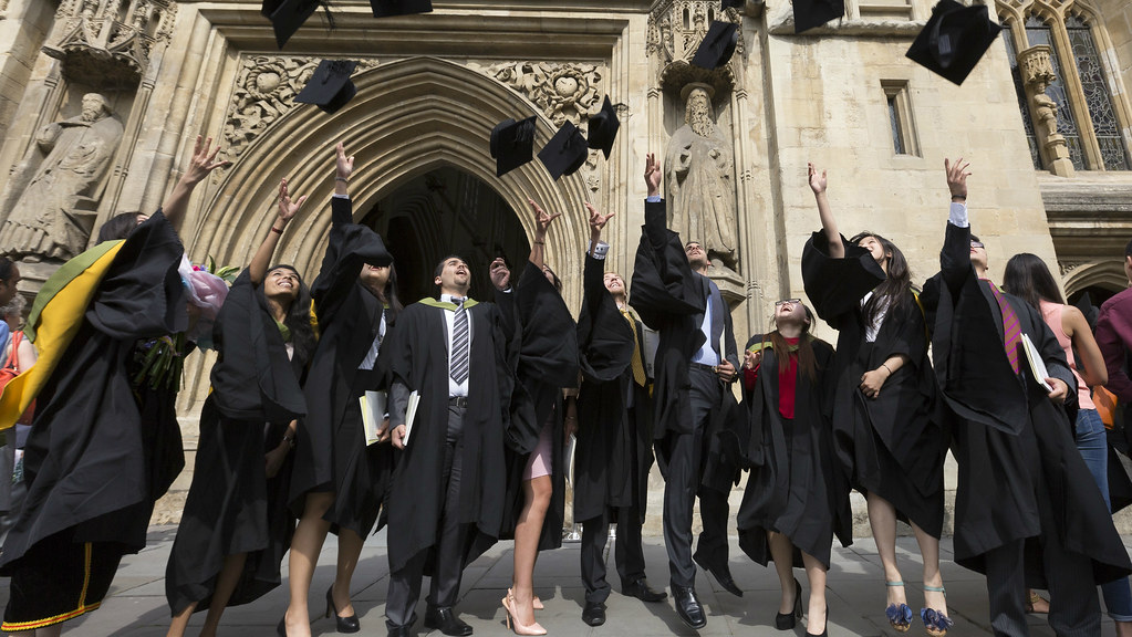 a groups of graduates throwing their mortar boards up in the air on graduation day