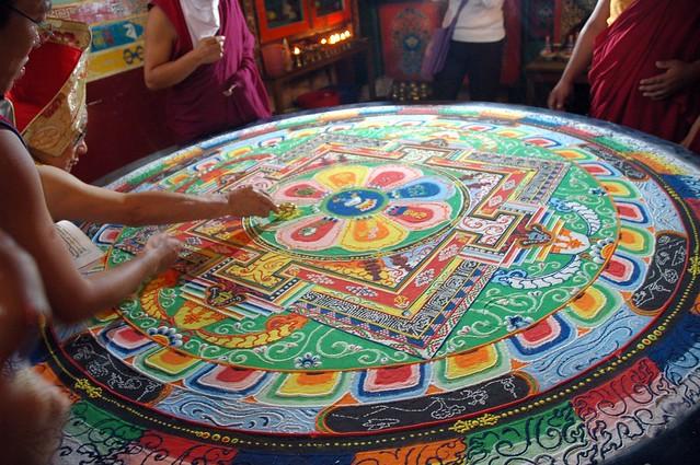 His Holiness Jigdal Dagchen Sakya draws a line with a vajra into the Hevajra sand mandala closing the glowing deity palace, on a circular table, monks and students attending, Sakya Lamdre, Tharlam Monastery of Tibetan Buddhism, Boudha, Kathmandu, Nepal