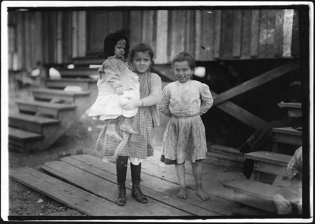 Millie, (about 7 years old) and Mary John (with baby) 8 years old. Both shuck oysters. This is Mary's second year, February 1911