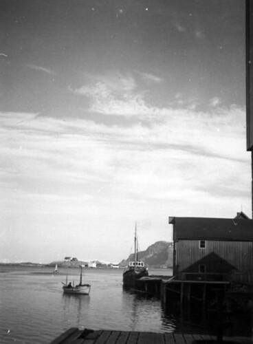 Jørgenskaia med skøyte ved kaia og en hvit motorbåt som ankommer