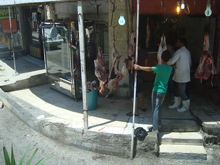 A butcher in Madaba hangs meat out to dry in front of his shop. | by NU Journalism in Amman