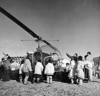 Mr. Alex Stevenson explaining   details of a Bell 47 helicopter from the CGS C.D. Howe to a group of Inuit at Pond Inlet, Northwest Territories / Monsieur Alex Stevenson, décrivant un hélicoptère Bell 47 du navire C.D. Howe de la Garde côtière canadi