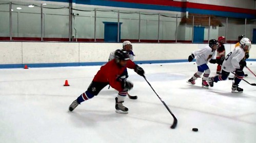 A hockey player playing keep away with the puck at a hockey clinic with Brad Perry | by Brad Perry