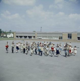 Group of children running toward photographer in school yard of Broadview Public School / Groupe d'enfants accourant vers le photographe dans la cour de récréation de l'école publique Broadview