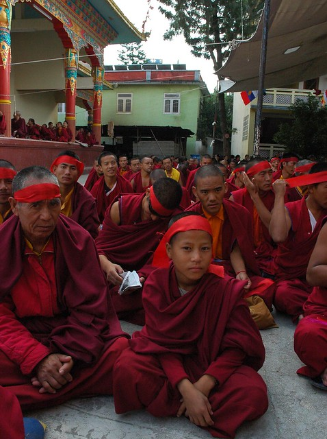 A composed young monk ready for initiation, Tibetan monks tying on red symbolic blindfolds for entry into the deity mandala, wearing traditional maroon garments, stage, Sakya Lamdre, Tharlam Monastery Courtyard, Boudha, Kathmandu, Nepal