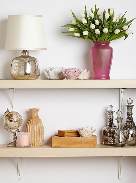 white tulips in a lavender glass vase metal lamp globe sand in bottles and art on shelves