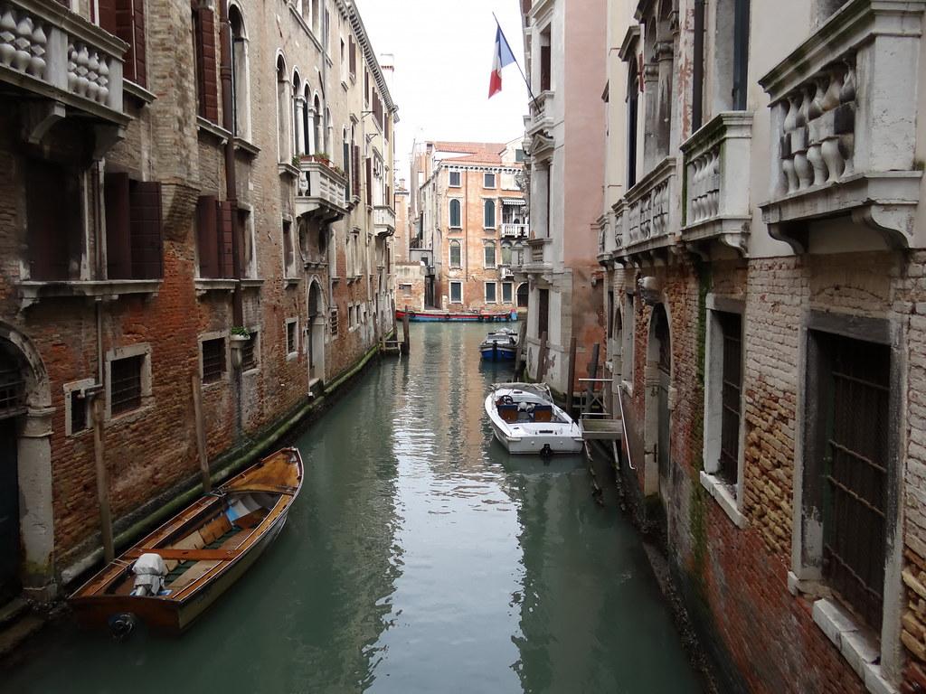 Venedig erscheint als vollendete Stadt in der Lagune, unter Brücken hindurch in der langen Gondel, schweben die Ufer der Kanäle vorbei, Paläste schweifen auch schön am Ufer entlang 00368