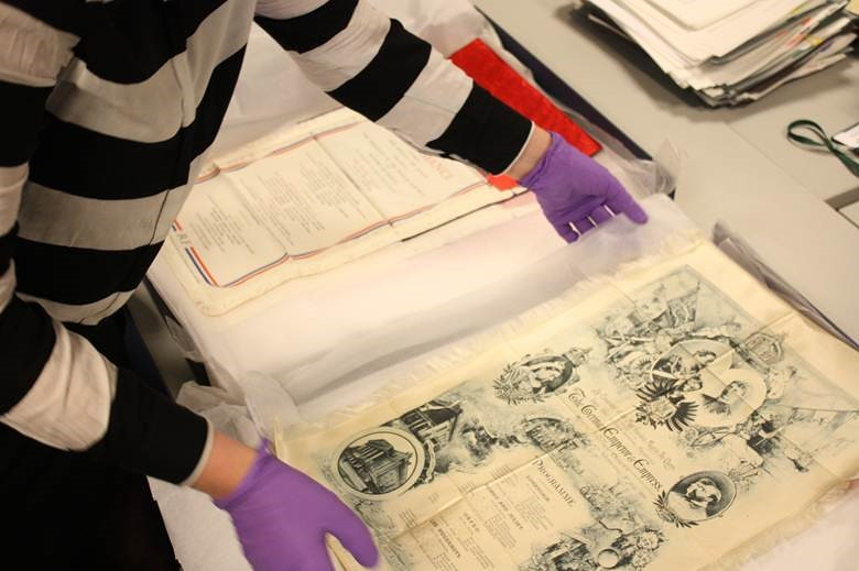 A member of staff working on a project to conserve the collection of silk programmes in ROH Collections © Royal Opera House