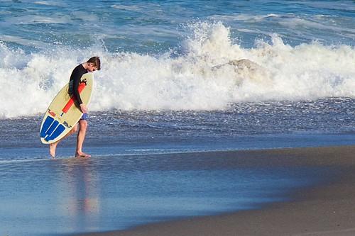 ocean beach sand surf surfer surfboard wetsuit