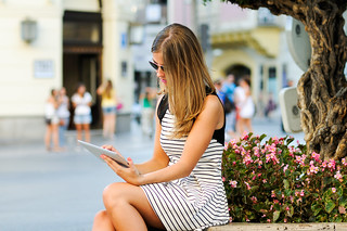 Attractive blonde woman with tablet computer in urban background | by javi_indy