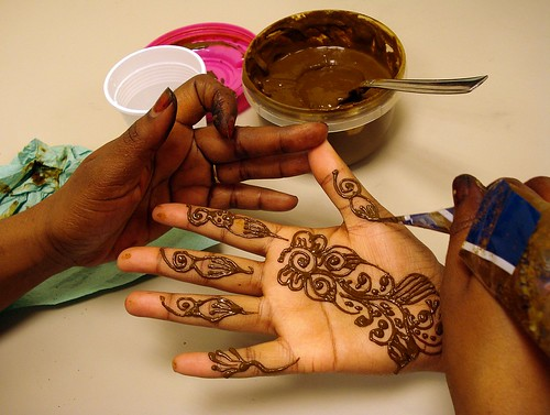 The hands of a dark-skinned person applying henna in intricate patterns to the palm of another person.  A tub of henna with a spoon in it is on the table next to them.