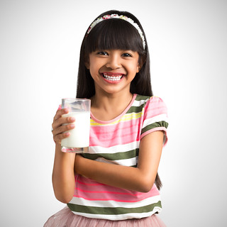 Little asian girl with a glass of milk, Grey background with clipping path   by Patrick Foto ;)