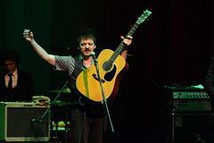 En la imagen se puede ver a Coque Malla levantando los brazos al público mientras sostiene la guitarra.  Fotografía cedida por Óscar Blanco Gutiérrez