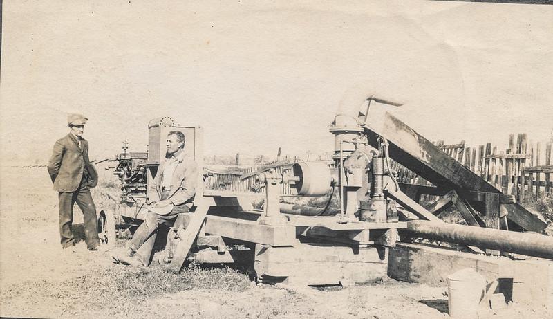 Men posing next to an irrigation pump